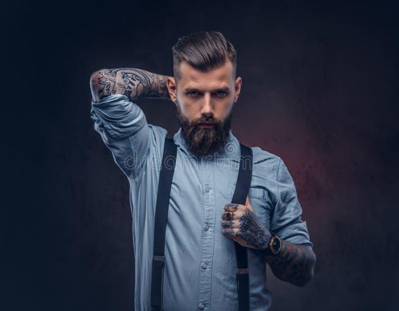 Retrato de un inconformista pasado de moda hermoso en una camisa azul y ligas imagen de archivo