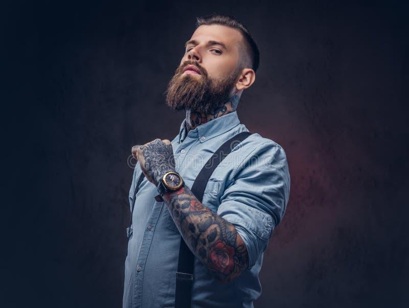 Retrato de un inconformista pasado de moda hermoso en una camisa azul y ligas imagen de archivo libre de regalías
