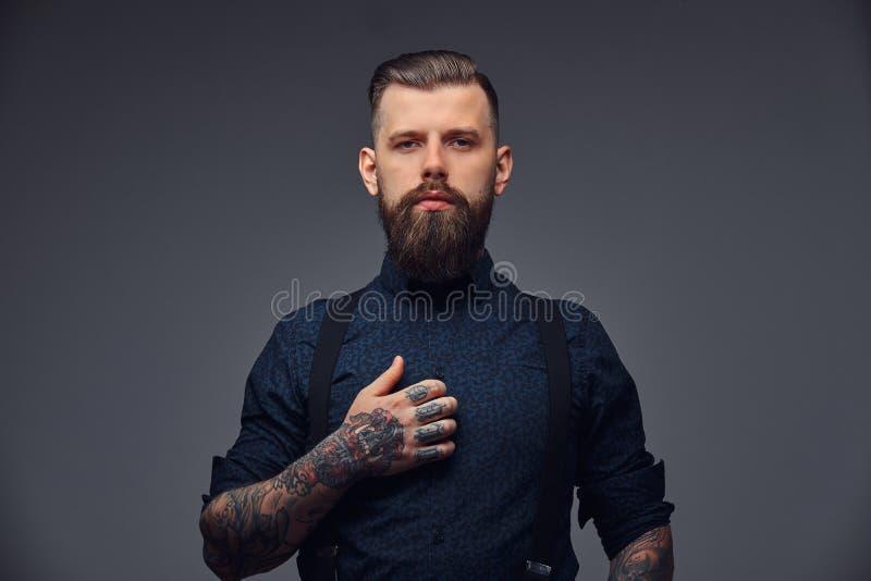 Retrato de un inconformista pasado de moda hermoso serio en camisa y ligas fotografía de archivo
