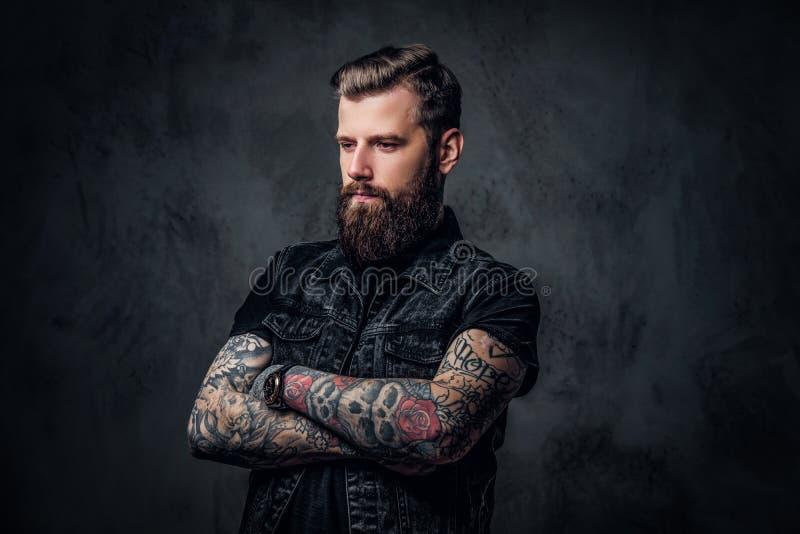 Retrato de un individuo barbudo elegante con las manos tatuadas Foto del estudio contra la pared oscura fotos de archivo libres de regalías