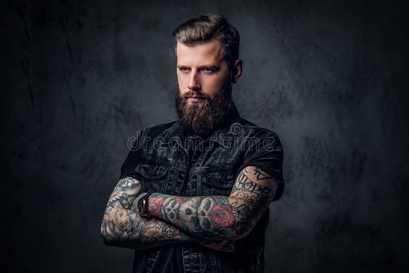Retrato de un individuo barbudo elegante con las manos tatuadas Foto del estudio contra la pared oscura foto de archivo