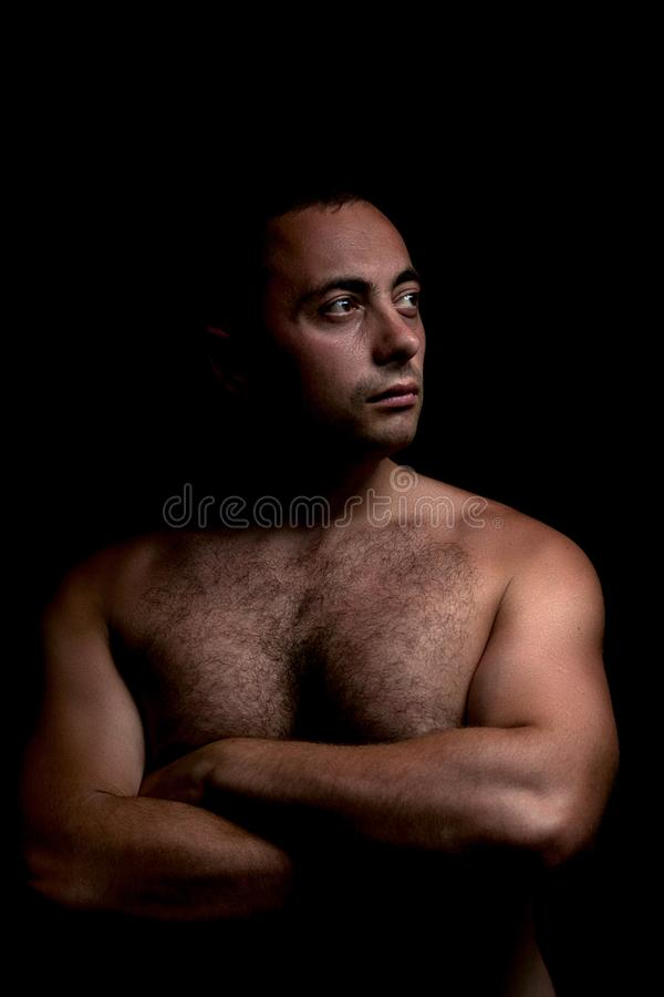 Retrato de un individuo con un torso desnudo en un oscuro en las sombras fotografía de archivo