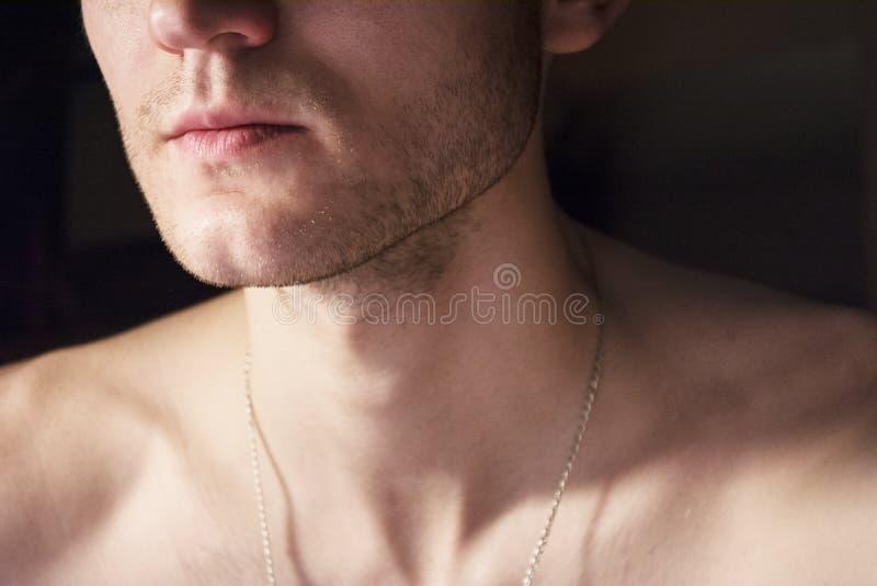 Retrato de un individuo hermoso con un torso desnudo Foto de un primer en un cuarto oscuro y de la luz de una lámpara Luz suave B foto de archivo
