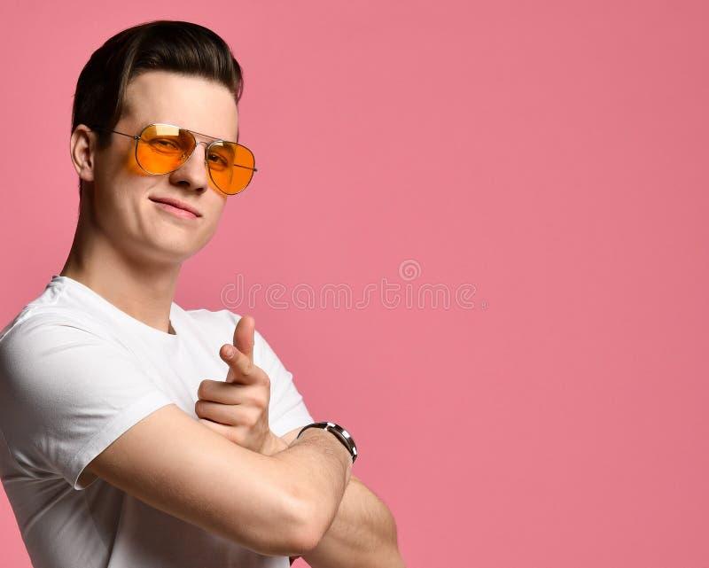 Retrato de un individuo de moda, moreno, lindo, positivo en una camiseta blanca que se?ala sus dedos ?ndices en usted imagen de archivo libre de regalías