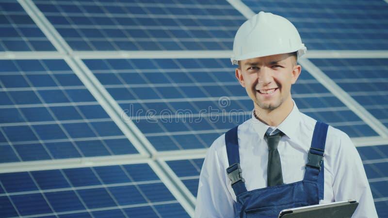 Retrato de un ingeniero joven acertado en el fondo de una estación de la energía solar foto de archivo libre de regalías