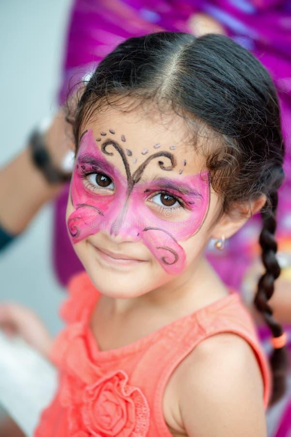 Retrato de un joven bonito lindo de cuatro años del niño de la muchacha con su cara pintada para la diversión en una fiesta de cu fotografía de archivo