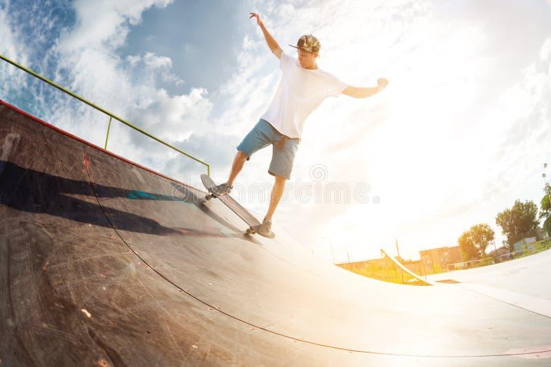 Retrato de un joven skateboarder haciendo un truco en su patineta en una rampa de medio tubo en un parque de patinaje en verano e fotos de archivo
