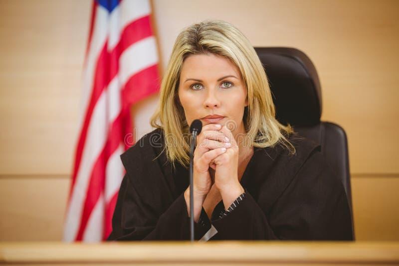 Retrato de un juez serio con la bandera americana detrás de ella foto de archivo libre de regalías