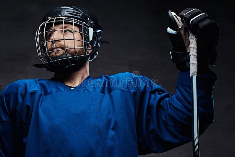 Retrato de un jugador barbudo del hielo-hockey en una ropa de deportes azul con el palillo del juego Tiro del estudio imágenes de archivo libres de regalías