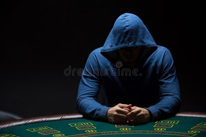 Retrato de un jugador de póker profesional que se sienta en la tabla de los pókeres fotografía de archivo