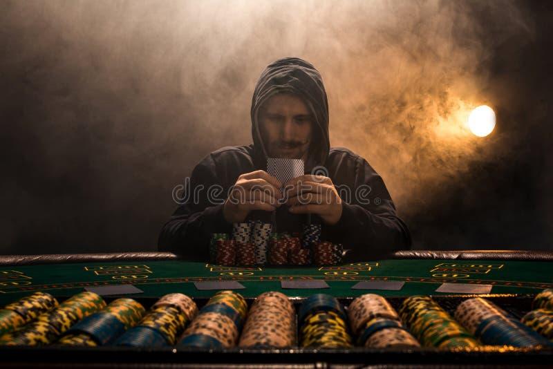 Retrato de un jugador de póker profesional que se sienta en la tabla de los pókeres fotos de archivo