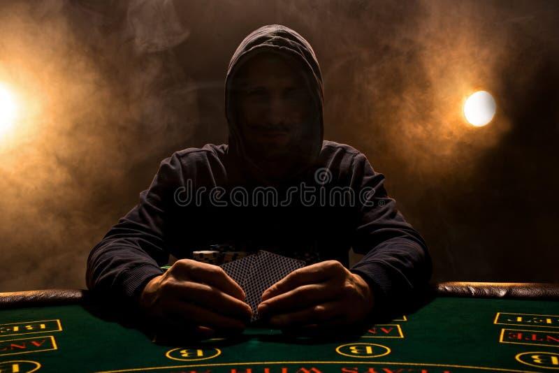 Retrato de un jugador de póker profesional que se sienta en la tabla de los pókeres foto de archivo libre de regalías