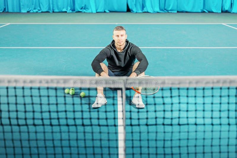 Retrato de un jugador de tenis de sexo masculino individuo joven con una estafa en sus manos que se sientan en la corte imagen de archivo