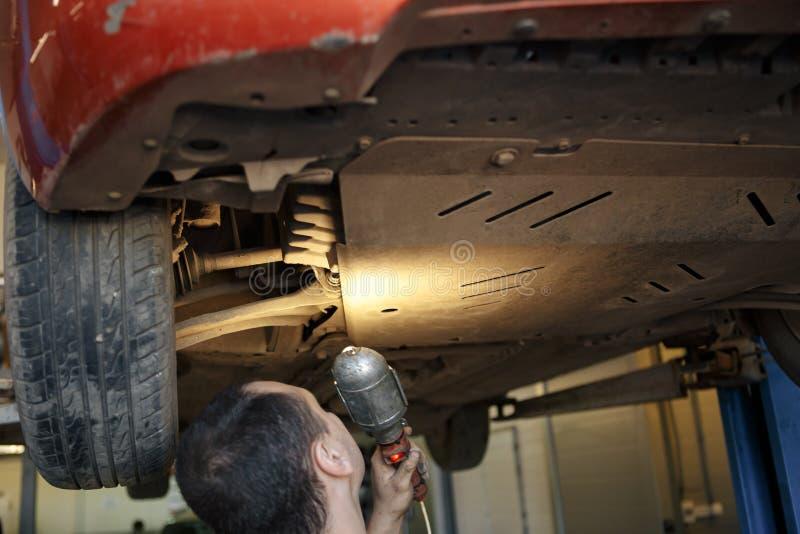 Retrato de un mecánico en el trabajo en su garaje foto de archivo