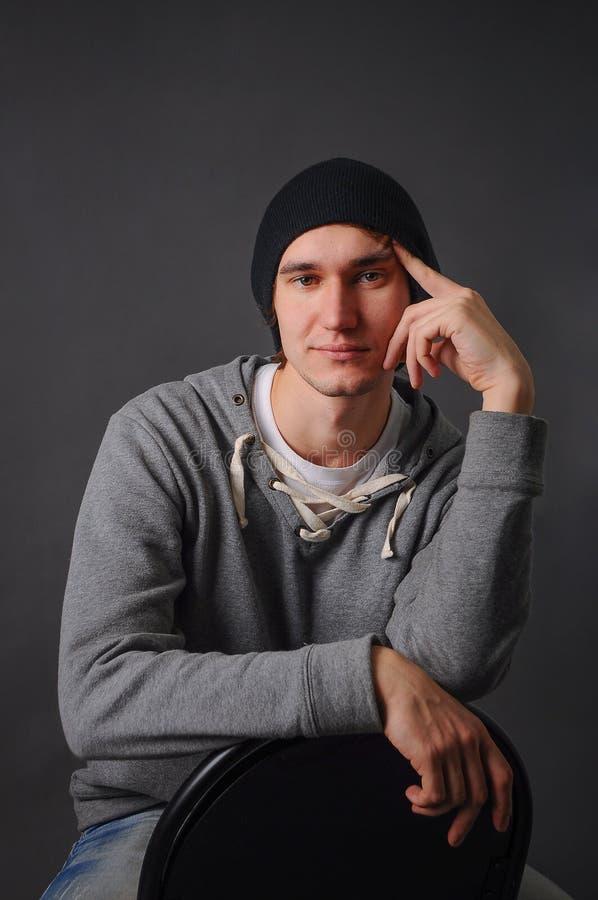 Retrato de un modelo masculino joven atractivo en el sombrero negro, los vaqueros y la camiseta gris, estudio, fondo gris oscuro foto de archivo