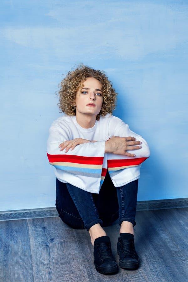 Retrato de un modelo triste del individuo del transexual con los ojos azules y el pelo rubio en la imagen de una muchacha en un f imágenes de archivo libres de regalías