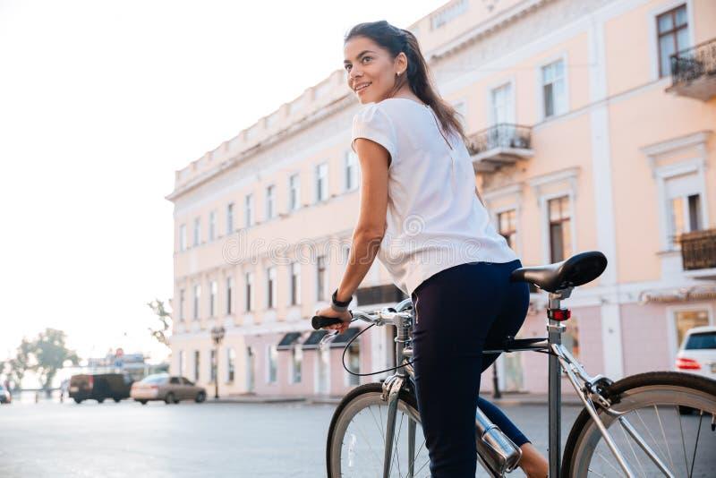 Retrato de un montar a caballo encantador de la mujer en la bicicleta imagen de archivo libre de regalías