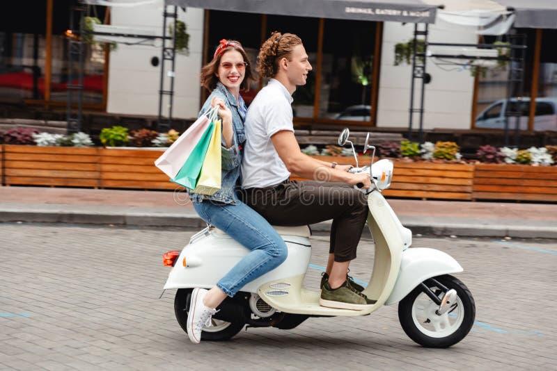 Retrato de un montar a caballo joven alegre de los pares en una moto foto de archivo libre de regalías