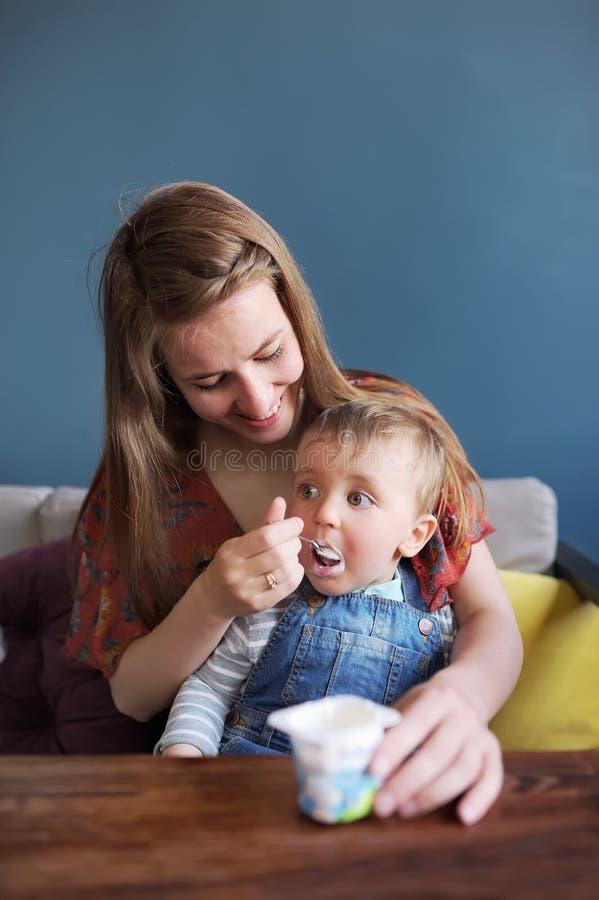 Retrato de un muchacho caucásico del niño con ojos grandes, que su madre con una cuchara está alimentando a helado en un café foto de archivo libre de regalías