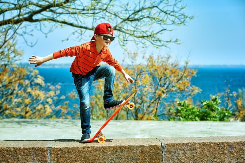 Retrato de un muchacho con un monopatín en el parque de la ciudad foto de archivo libre de regalías