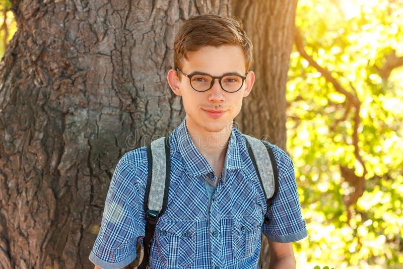 Retrato de un muchacho en empollón de los vidrios en un fondo del árbol imagen de archivo libre de regalías