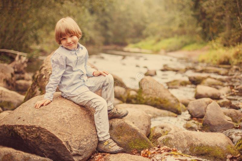 Retrato de un muchacho en un fondo de la naturaleza El niño se está sentando en las rocas por el río fotos de archivo