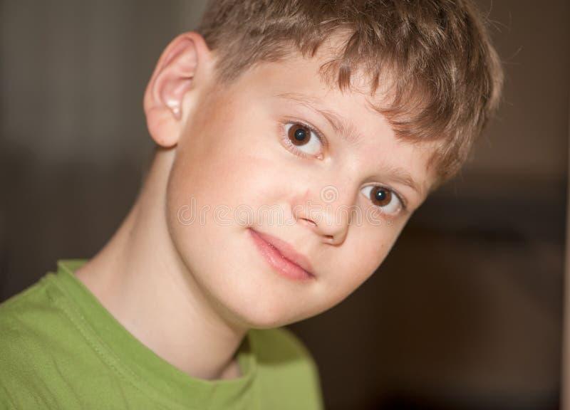 Retrato de un muchacho en una camiseta verde clara fotos de archivo