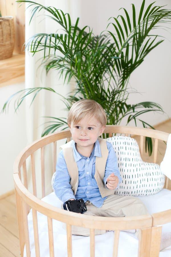 Retrato de un muchacho feliz que juega en una choza de bebé El muchacho se sienta solamente en un pesebre en el cuarto de niños E foto de archivo