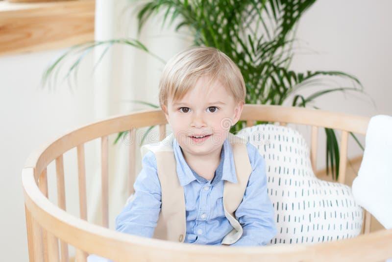 Retrato de un muchacho feliz que juega en una choza de bebé El muchacho se sienta solamente en un pesebre en el cuarto de niños E imagen de archivo libre de regalías