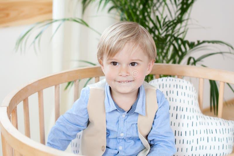 Retrato de un muchacho feliz que juega en una choza de bebé El muchacho se sienta solamente en un pesebre en el cuarto de niños E foto de archivo libre de regalías