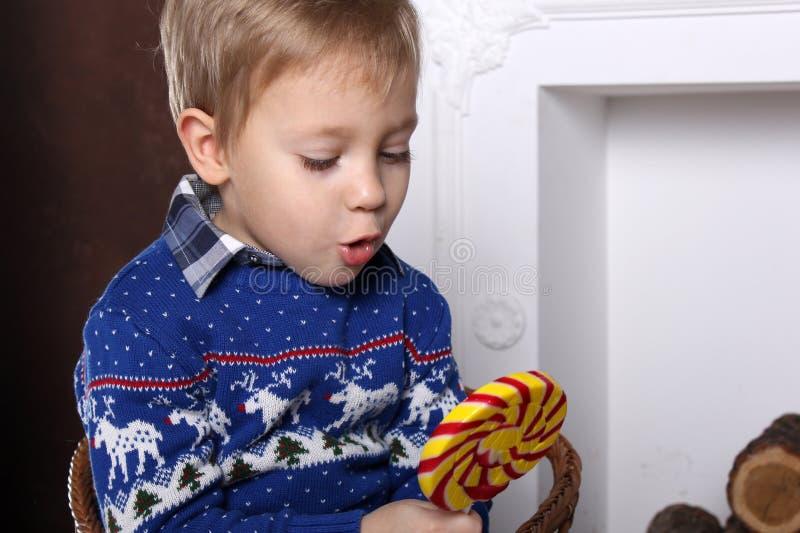 Retrato de un muchacho joven con una piruleta colorida grande deliciosa fotos de archivo