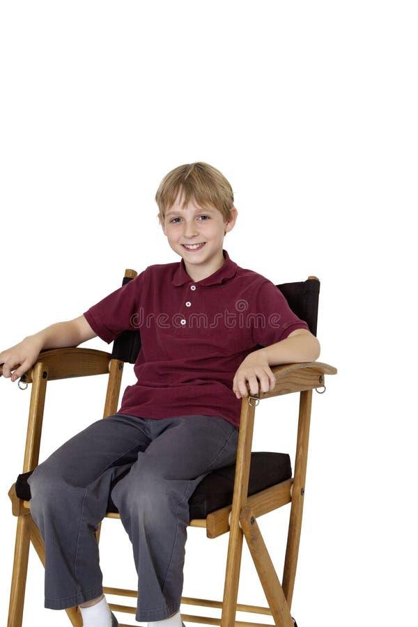 Retrato de un muchacho pre-adolescente feliz que se sienta en la silla del director sobre el fondo blanco fotos de archivo