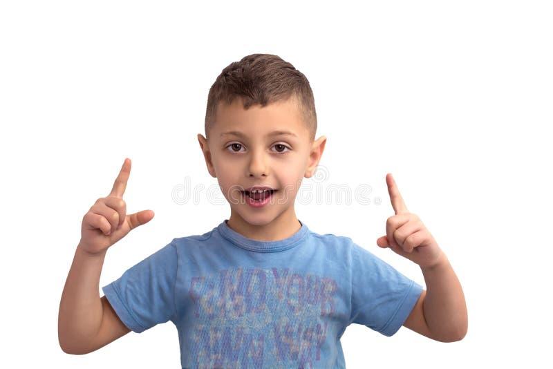 Retrato de un muchacho que sostiene dos fingeres para arriba aislados en el fondo blanco imagenes de archivo