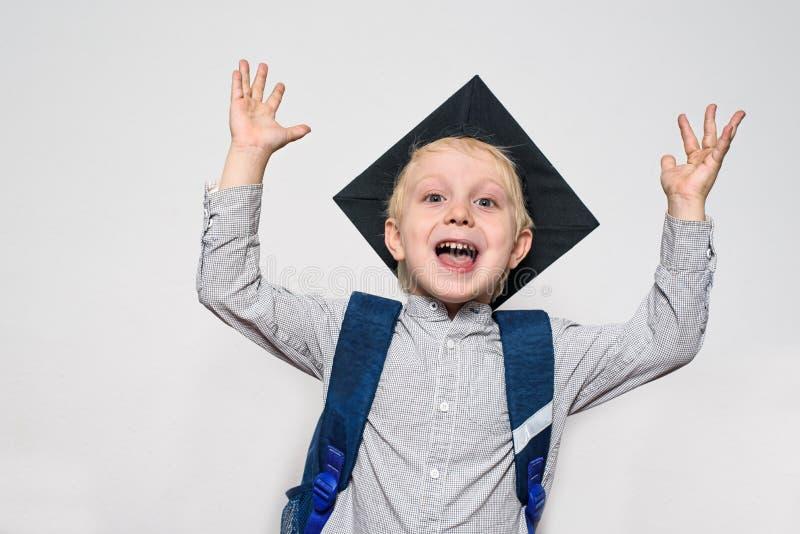 Retrato de un muchacho rubio alegre con el sombrero académico y un bolso de escuela Manos para arriba Fondo blanco imágenes de archivo libres de regalías