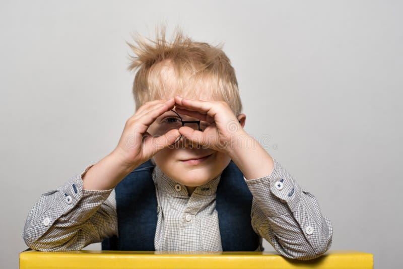 Retrato de un muchacho rubio divertido con vidrios y una mochila de la escuela en un fondo blanco Concepto de la escuela fotos de archivo libres de regalías