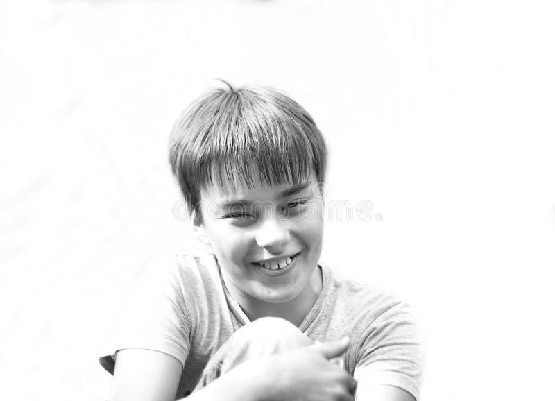 Retrato de un muchacho sonriente lindo de once años en un fondo blanco foto de archivo