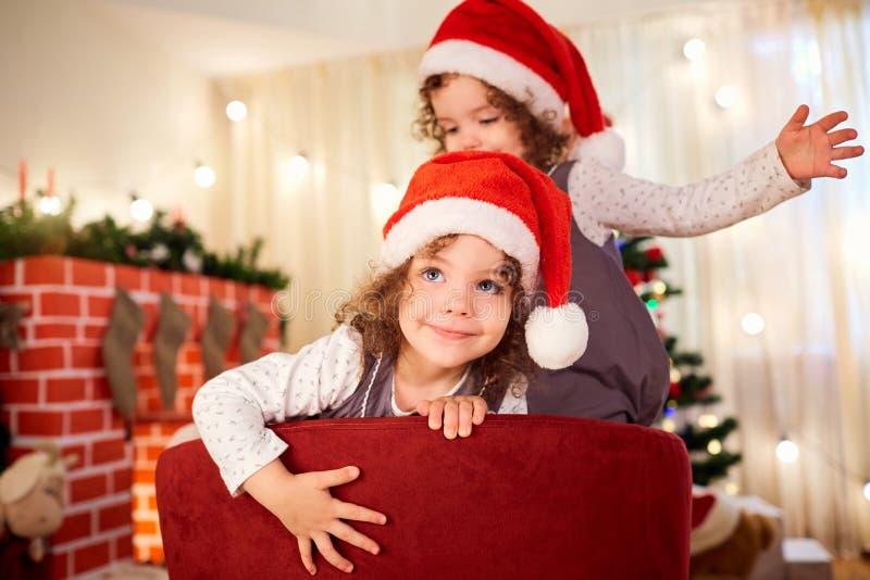 Retrato de un niño en la Navidad Muchacha linda rizada en el sombrero a de santa foto de archivo libre de regalías