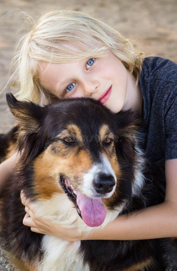 Retrato de un niño feliz lindo que abraza su perro casero imagen de archivo