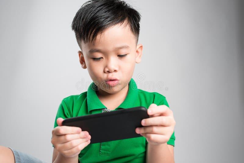 Retrato de un niño lindo divertido que juega a los juegos en smartphone aislados sobre fondo gris foto de archivo