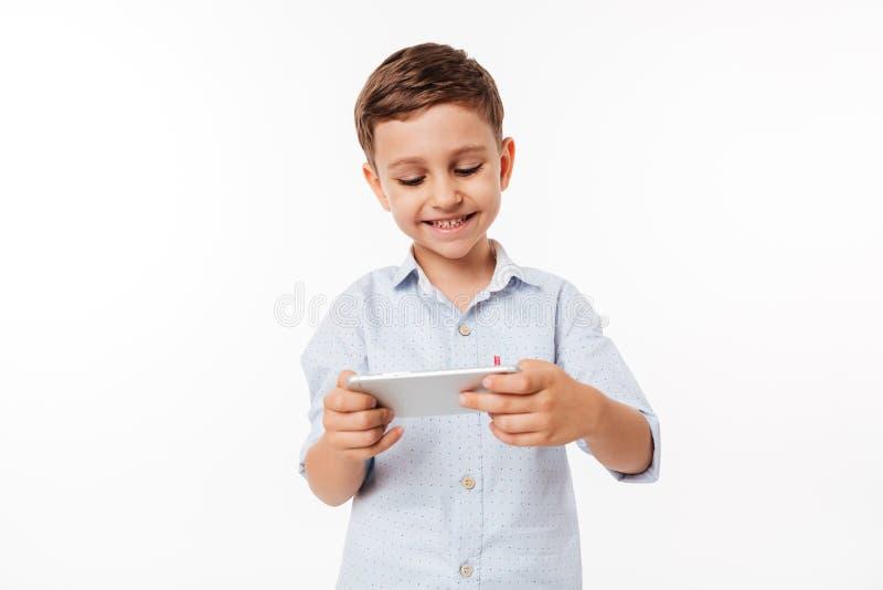 Retrato de un niño lindo que juega a juegos en smartphone foto de archivo