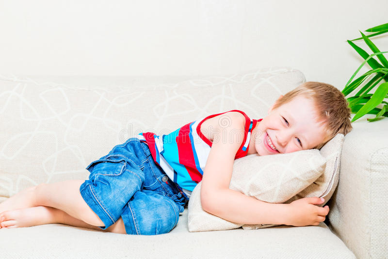 Retrato de un niño pequeño de risa en el sofá foto de archivo