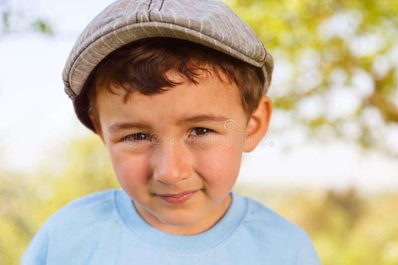 Retrato de un niño pequeño del niño del niño con la cara al aire libre del casquillo al aire libre imagen de archivo