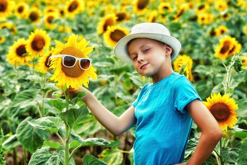 Retrato de un niño pequeño en un campo con un girasol floreciente fotos de archivo