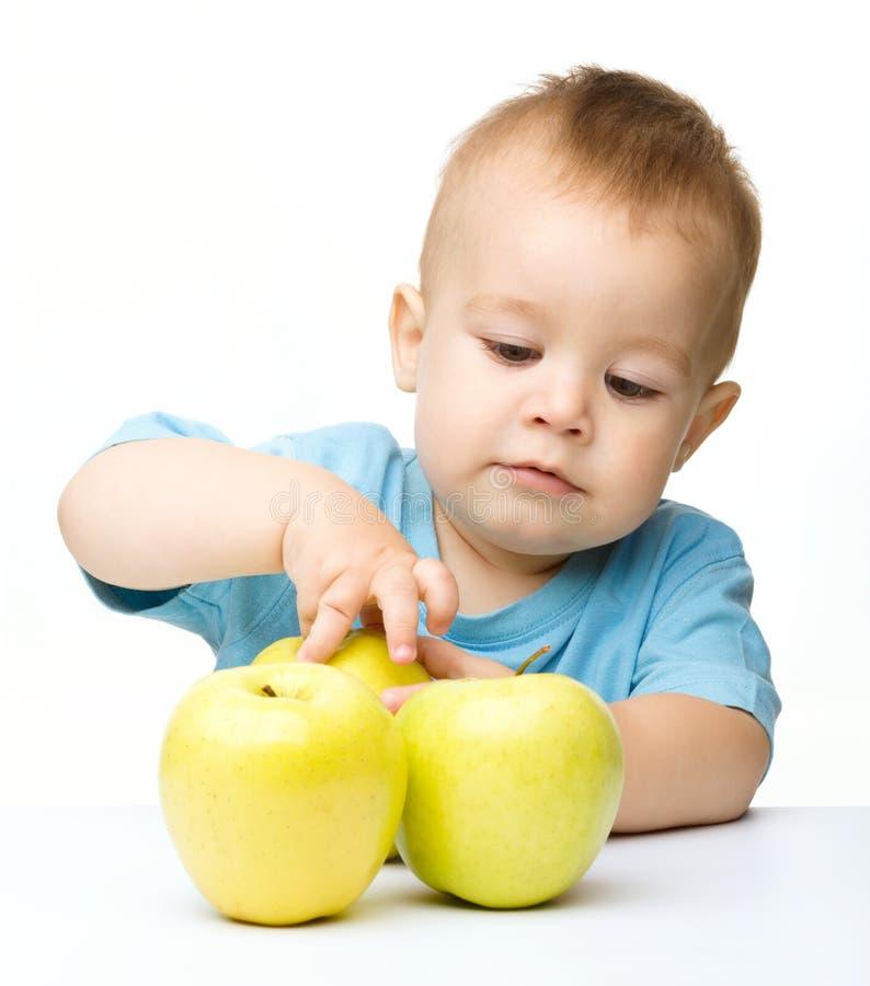 Retrato de un niño pequeño lindo con las manzanas amarillas fotografía de archivo