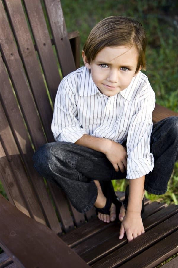 Retrato de un niño pequeño lindo en silla del adirondack imagen de archivo libre de regalías