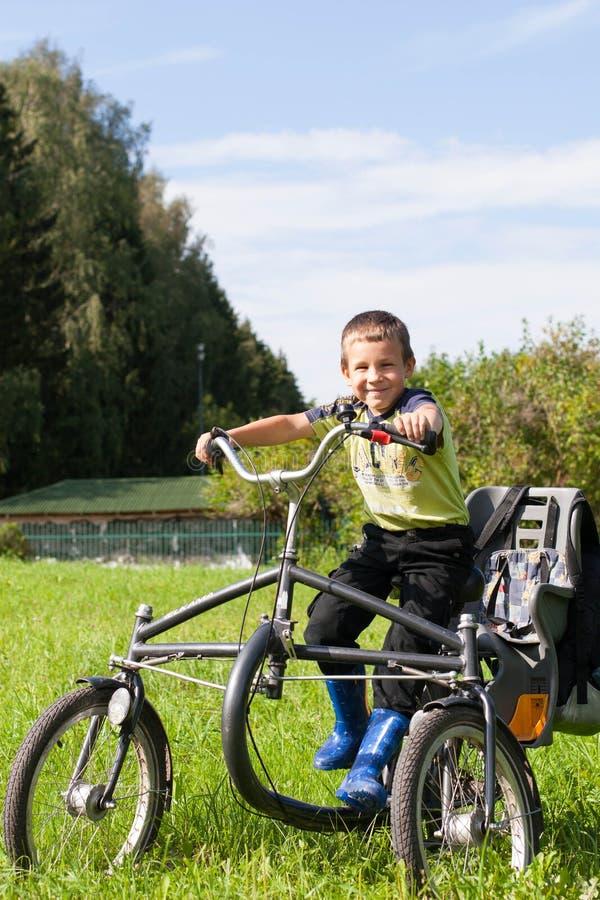 Retrato de un niño pequeño que monta un triciclo en el parque imágenes de archivo libres de regalías