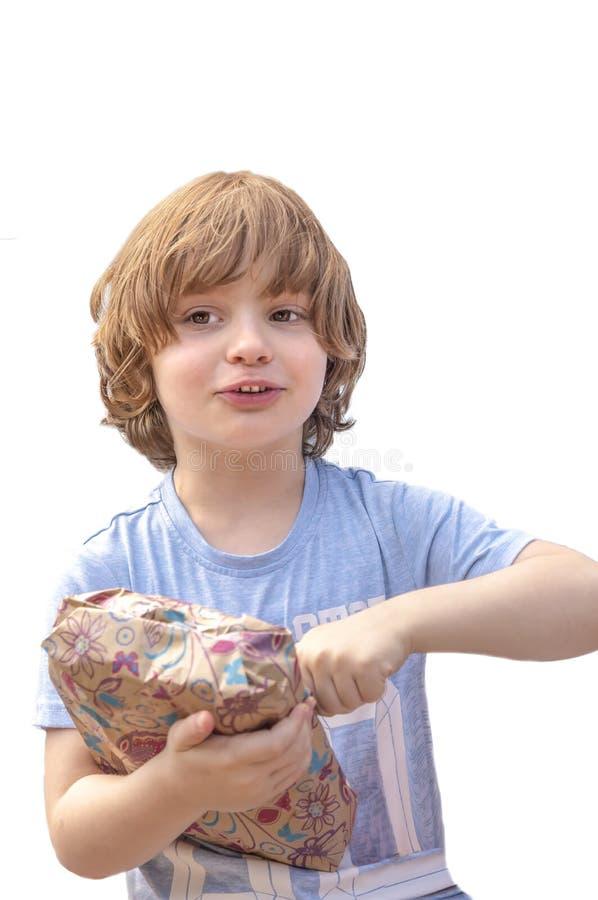 Retrato de un niño pequeño que regocijó su presente de cumpleaños, en un fondo blanco fotografía de archivo