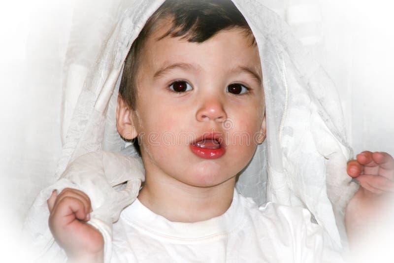 Retrato de un niño pequeño que se divierte con las cortinas blancas en su hogar imagenes de archivo