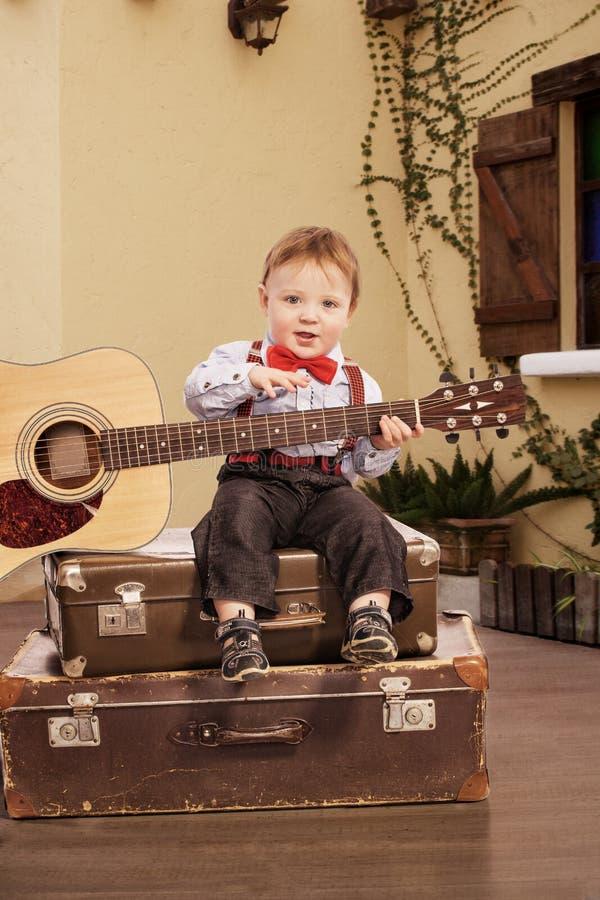 Retrato de un niño pequeño romántico que se sienta con la guitarra fotos de archivo