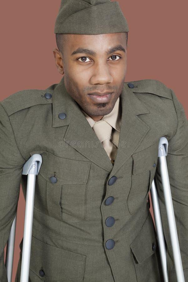 Retrato de un oficial del ejército de los E.E.U.U. del afroamericano con las muletas sobre fondo marrón imagen de archivo